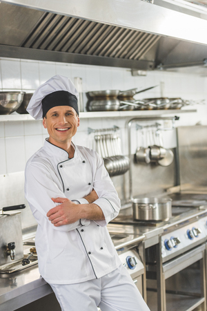 smiling chef standing with crossed arms and looking at camera at restaurant kitchen Stockfoto