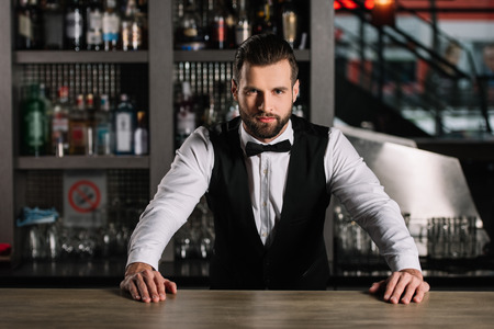 handsome bartender leaning on bar counter and looking at camera