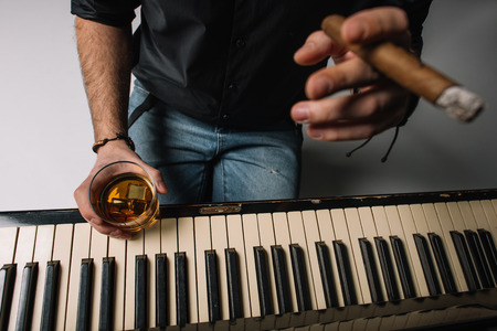 cropped shot of man sitting in front of piano with cigar and glass of whiskey 写真素材 - 111366859