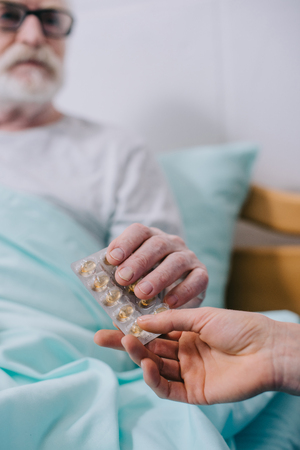 Close-up view of senior patient taking medications from doctor