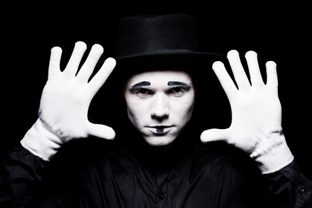 mime showing hands isolated on black Zdjęcie Seryjne