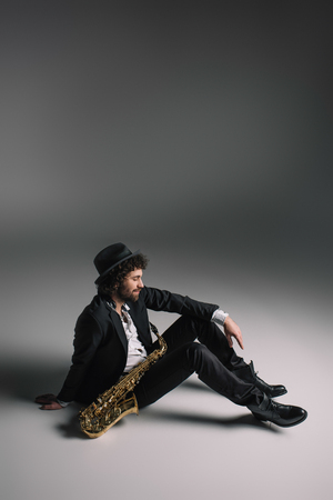 handsome musician sitting on floor with saxophone 스톡 콘텐츠