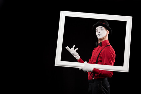 elegant mime gesturing in frame isolated on black Фото со стока