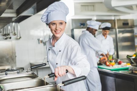 chef attraente che frigge cibo in olio nella cucina del ristorante e guarda lontano?