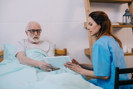 Senior patient and caregiver using tablet Stock Photo