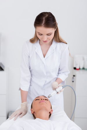 young woman getting facial treatment in cosmetology salon Stock Photo