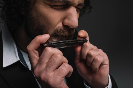 close-up portrait of expressive musician playing harmonica on black 免版税图像 - 111367142