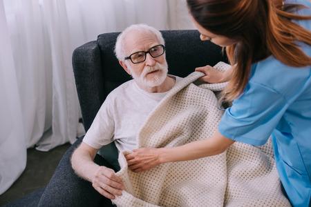 Caregiver covering senior patient with plaid