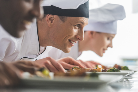 smiling multiethnic chefs sniffing cooked food at restaurant kitchen