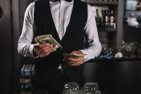 cropped image of bartender counting tips