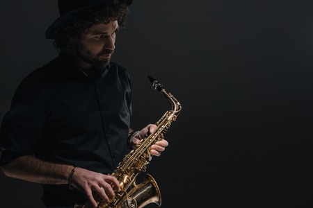 young musician playing saxophone on black Stock Photo