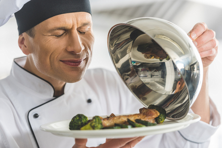 handsome chef sniffing dish at restaurant kitchen with closed eyes Imagens