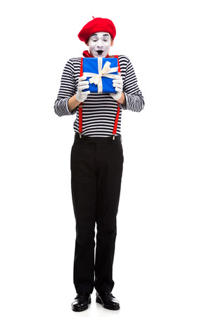surprised mime looking at gift box isolated on white