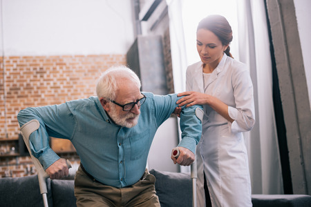 Doctor holding old male patient with crutches
