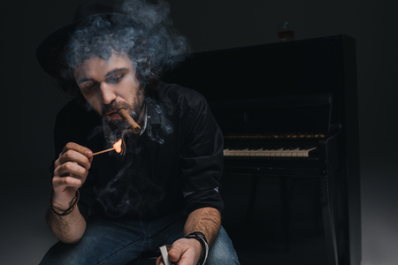 handsome bearded musician smoking cigar in front of piano on black 写真素材