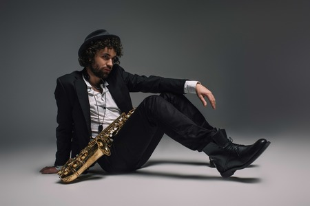 handsome stylish musician sitting on floor with saxophone Stock Photo