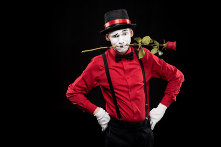mime grimacing and holding red rose in mouth isolated on black Фото со стока