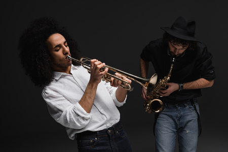 duet of musicians playing trumpet and sax on black Stock Photo