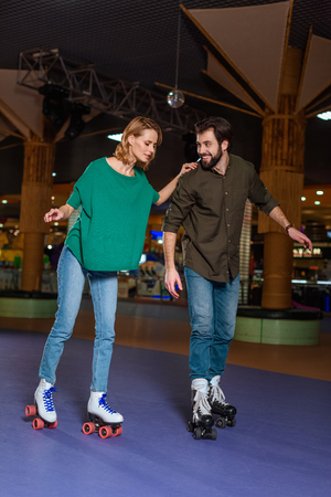 young couple skating together on roller rink