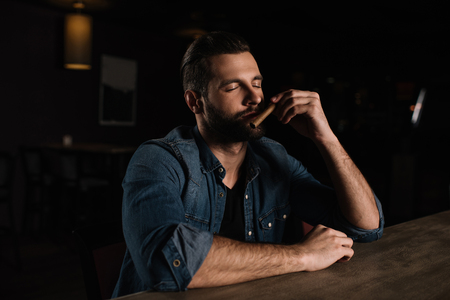 visitor sitting at bar counter and sniffing cigar