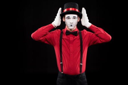 mime covering ears with hands isolated on black Banque d'images - 111367399