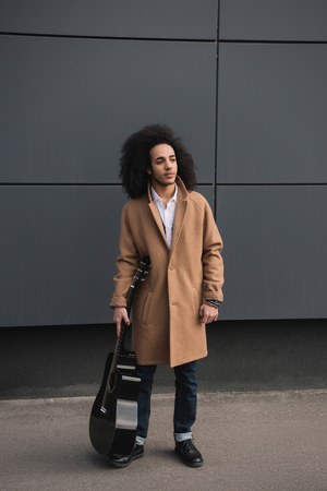 stylish street musician standing with guitar outdoors