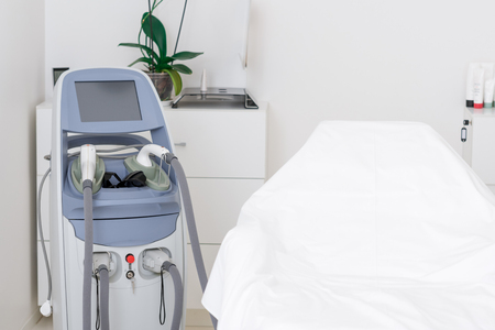 close up view of cosmetology apparatus and empty massage table in salon Reklamní fotografie