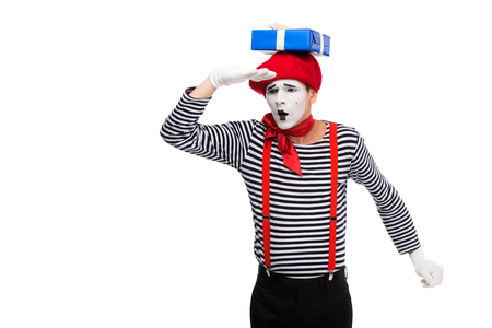 mime looking away with gift box on head isolated on white