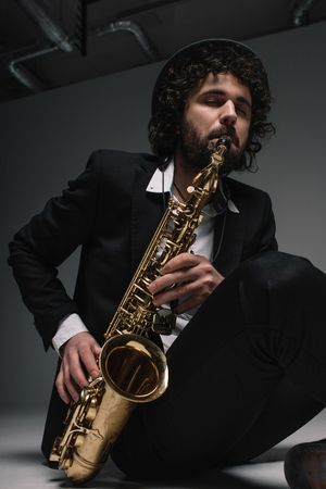 artistic musician playing saxophone while sitting on floor 스톡 콘텐츠