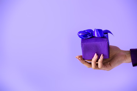 cropped view on female hand holding purple gift, isolated on ultra violet