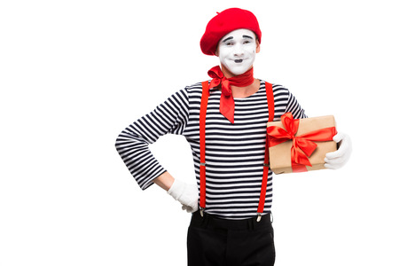 smiling mime holding present box and looking at camera isolated on white