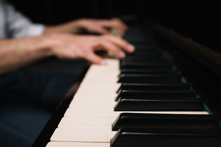 cropped shot of musician playing piano