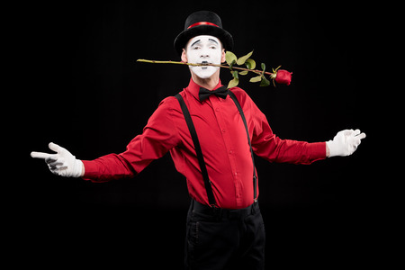 mime holding red rose in mouth and standing with open arms isolated on black Zdjęcie Seryjne