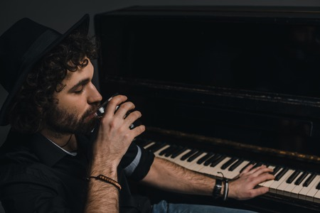 handsome musician drinking whiskey and playing piano 写真素材