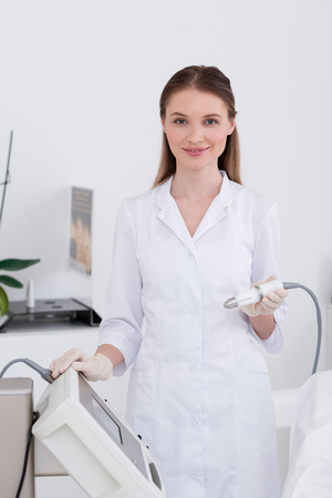 Retrato de joven cosmetóloga en bata blanca y guantes de látex con aparato en el salón