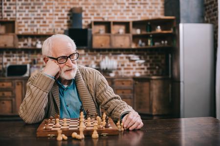 Bored senior man playing chess