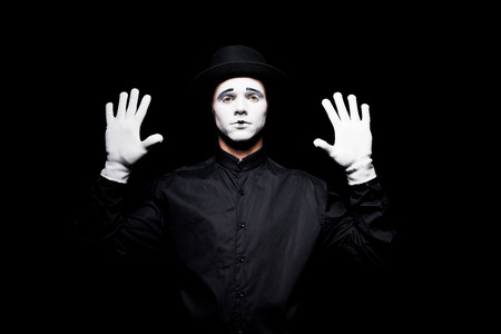 mime pretending touching something with hands isolated on black Zdjęcie Seryjne