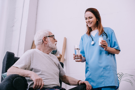 Nurse standing by senior man taking medications Stock Photo