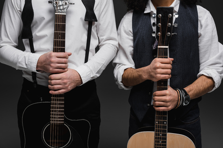 cropped shot of duet of musicians with acoustic guitars