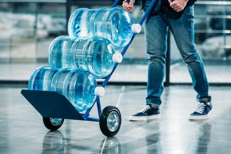 Loader pushing cart with water bottles
