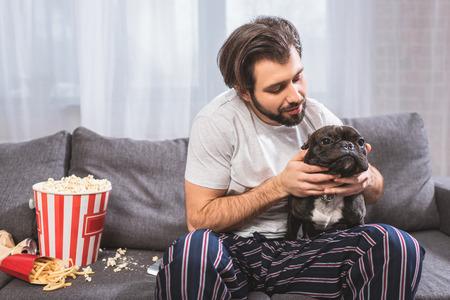 handsome loner hugging bulldog on sofa in living room