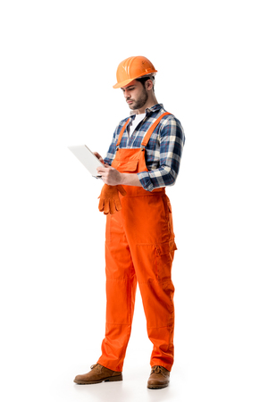 Young repairman in orange overall and hard hat using digital tablet isolated on white