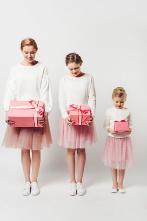 smiling mother and little daughters in similar pink tutu tulle skirts with wrapped gifts isolated on grey Banque d'images