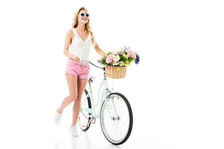 Young girl in sunglasses standing by bicycle with flowers in basket isolated on white