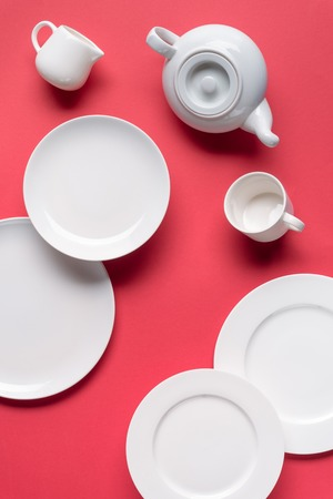 White plates with teapot and cup on red background Zdjęcie Seryjne