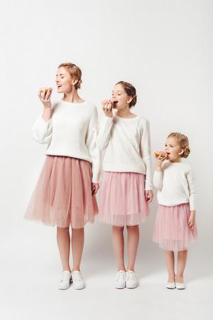 familie in soortgelijke kleding die zoete donuts eet die op grijs worden geïsoleerd