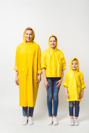 happy mother and daughters in yellow raincoats standing in row on white Stock Photo