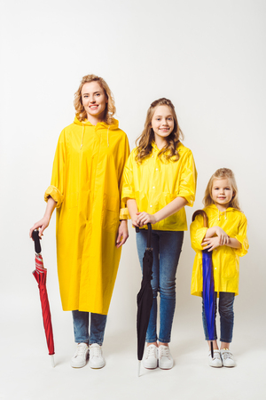 mother and daughters in yellow raincoats with umbrellas on white 스톡 콘텐츠