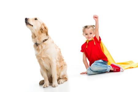 Beige dog sitting with happy gesturing supergirl in yellow cape isolated on white