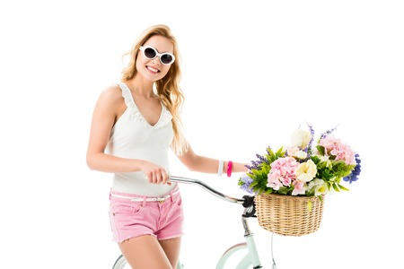 Blonde woman in sunglasses holding bicycle with flowers in basket isolated on white